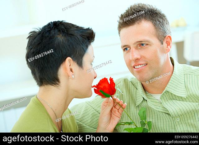 Romantic portrait of love couple. Woman smelling red rose, man smiling at her