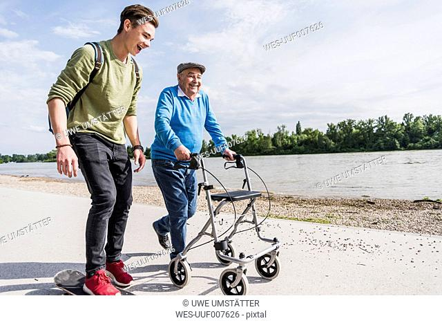 Grandfather and grandson strolling together at riverside