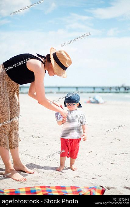 2 years old boy with his mother drinking juice at the beach
