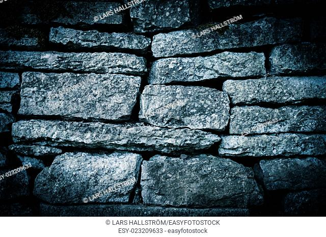 Backdrop of an old and weathered stone wall made of big blocks. With a worn grunge atmosphere this architectural detail gives the tone and feeling of a rough...