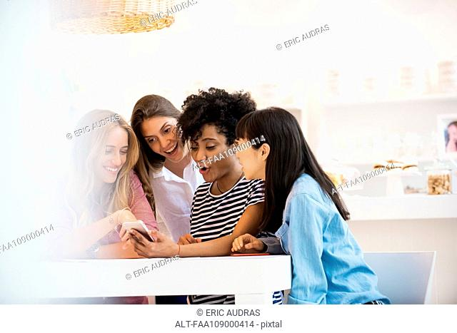 Group of friends looking at smartphone together in cafe