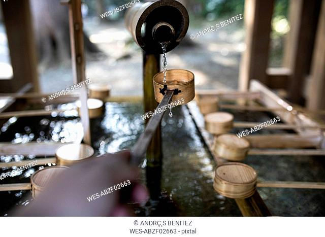 Young woman catching water for the ritual of hand washing in a Tokyo temple, Japan
