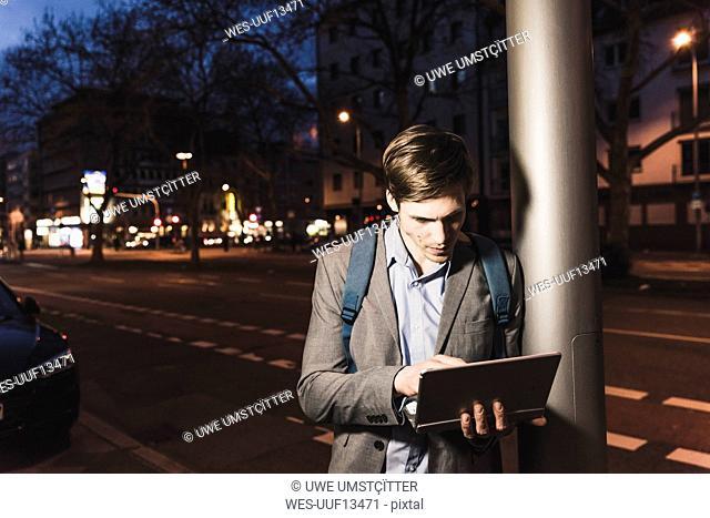 Businessman using laptop on urban street at night
