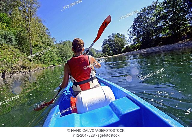 Young woman kayaking in Sella River, Asturias, Spain