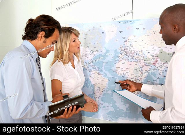 Business team looking at world map