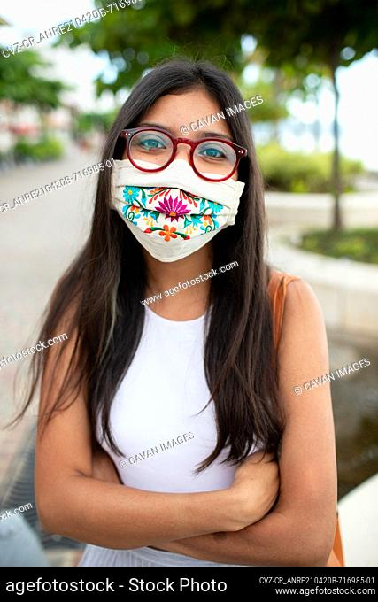 Pretty young woman smiling with facemask and glasses