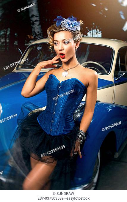 Beautiful woman in blue corset, black skirt and elegant hat posing over retro car