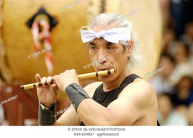Man playing flute while others are playing taiko drums during musical performance. Gion Matsuri (festival), Yasaka shrine, Kyoto, Japan