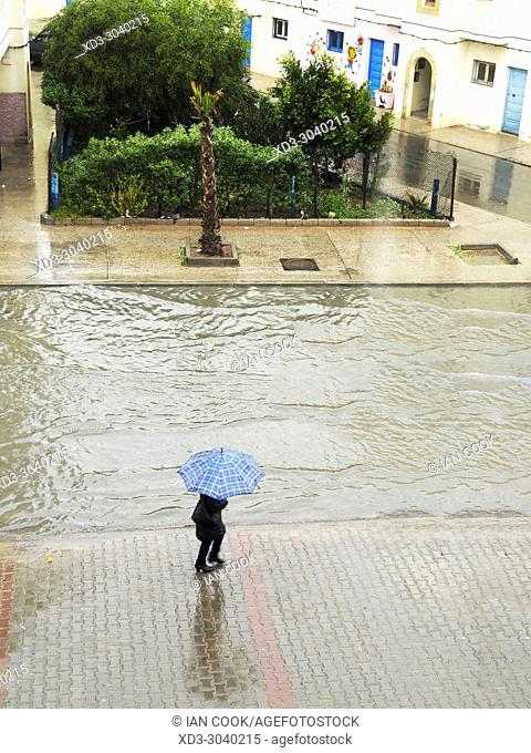 woman with umbrella on a flooded street, Lotissement 5, Essaouira, Morocco