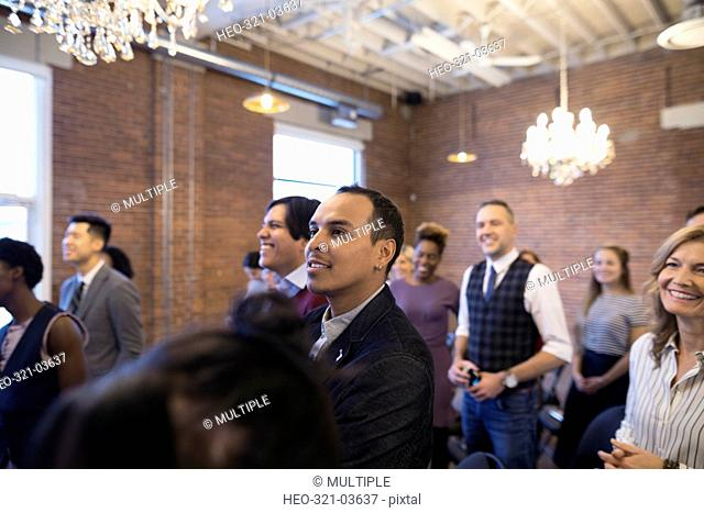 Smiling businessman listening in conference audience