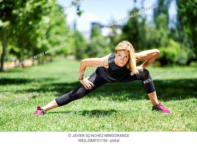 Mature woman exercising on a meadow in a park
