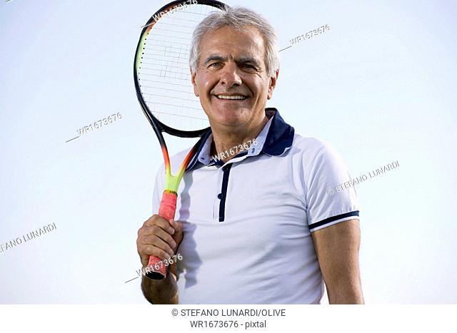 Mature man holding tennis racquet