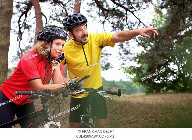 Mountain biking couple using smartphone navigation in forest