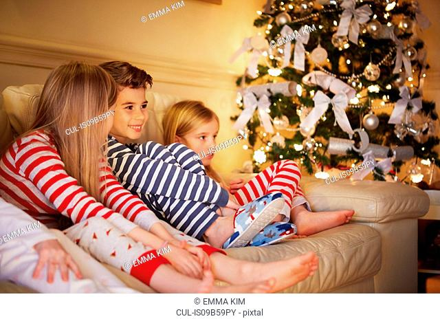 Boy and girls in striped pyjamas on sofa at christmas