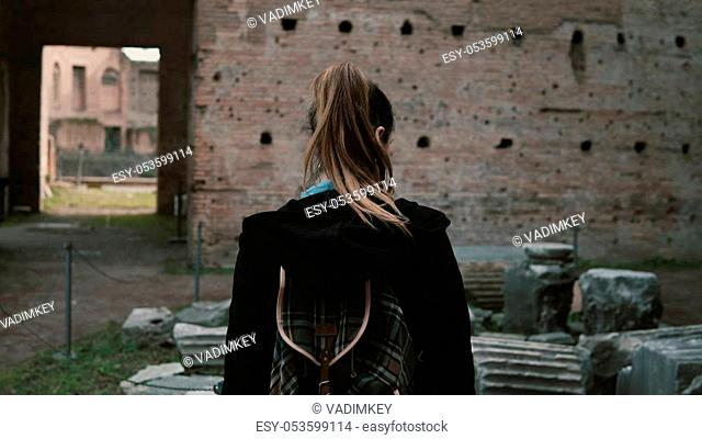 young tourist is walking around Rome, Italy, learning about its ancient history. The woman is touching the brick wall of the antique castle