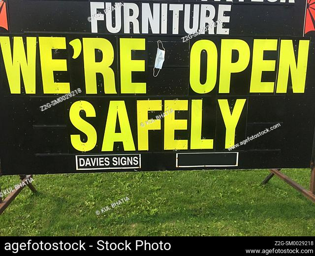 We're open safely, sign with a suggestion for wearing a mask, in a shopping area, Ontario, Canada. Many stores and businesses are responding in this way to the...