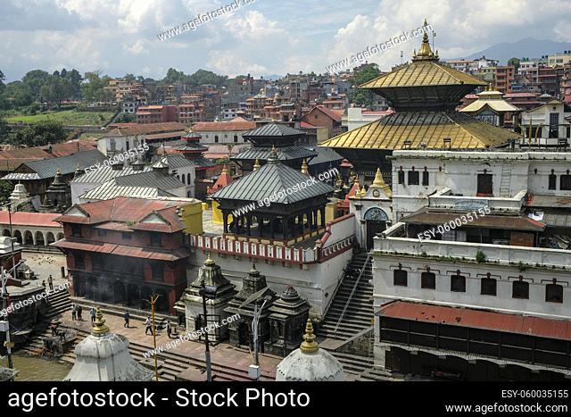 Kathmandu, Nepal - September 2021: People making offerings on the ghats of the Pashupatinath Temple on the Bagmati River on September 29, 2021 in Kathmandu