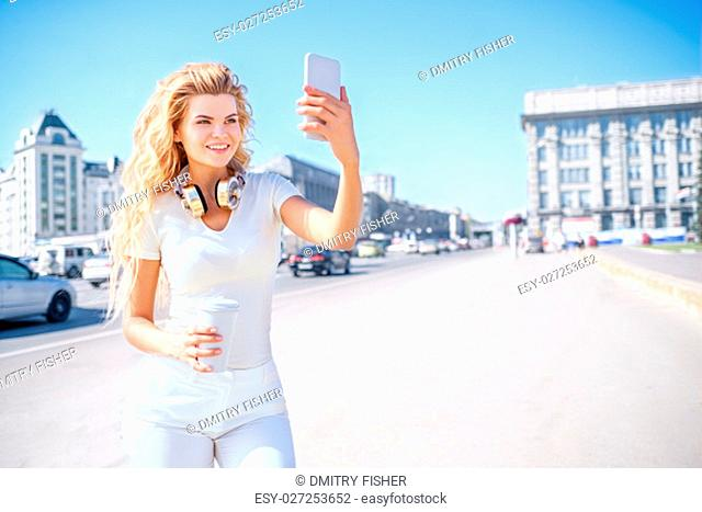 Beautiful young woman with music headphones and a take away coffee cup, taking picture of herself, selfie against urban city background