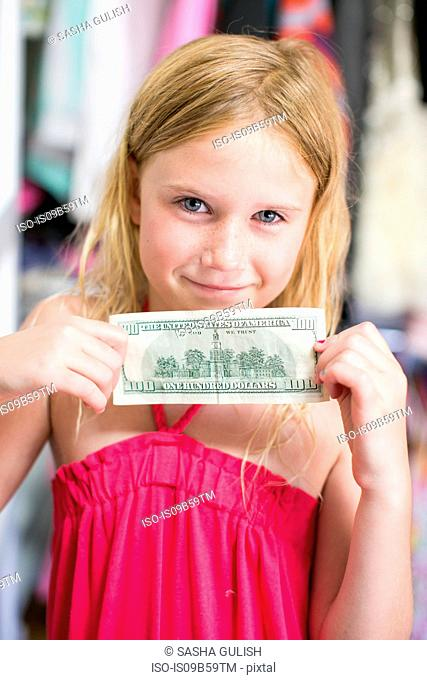 Portrait of girl holding dollar bill