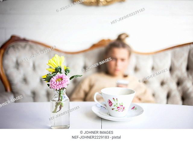 Cup and flowers on table, girl on background