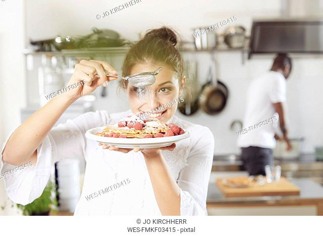 Portrait of young woman sprinkling icing sugar on waffles in the kitchen