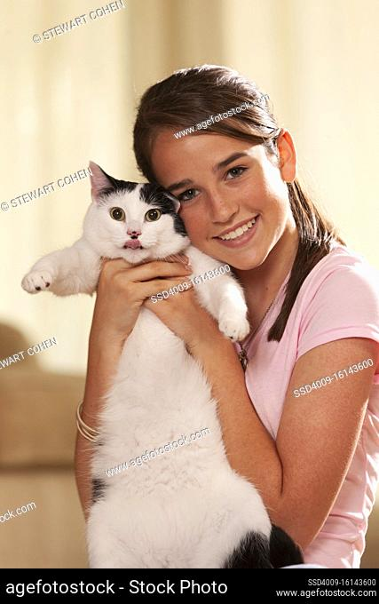 Portrait of teenage caucasian girl sitting on rug in living room holding up her pet cat