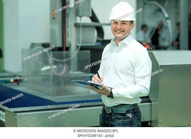 Engineer working in factory. Holding check-list and supervising