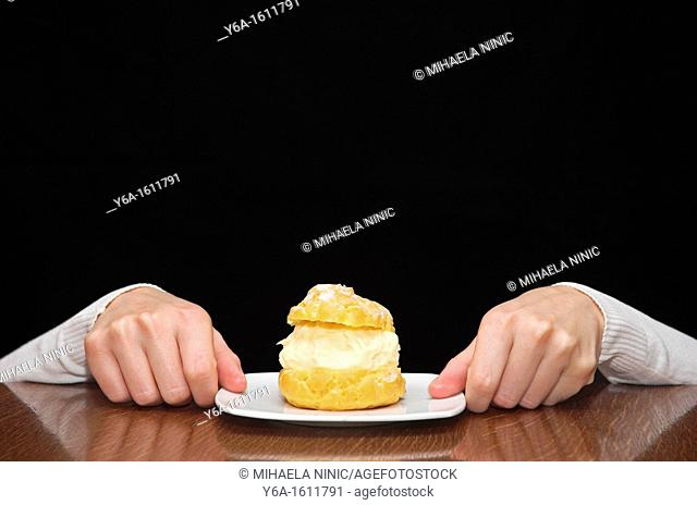 Woman's hands reaching for a cake on table