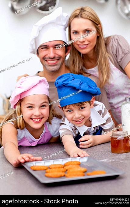 Happy children and parents eating cookies after baking