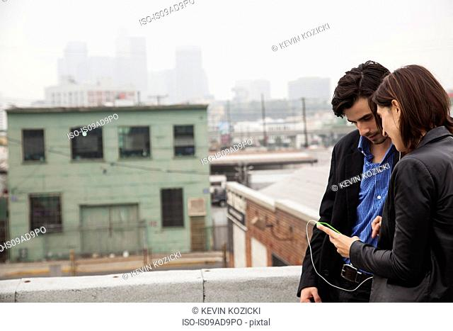 Couple listening to music on city rooftop