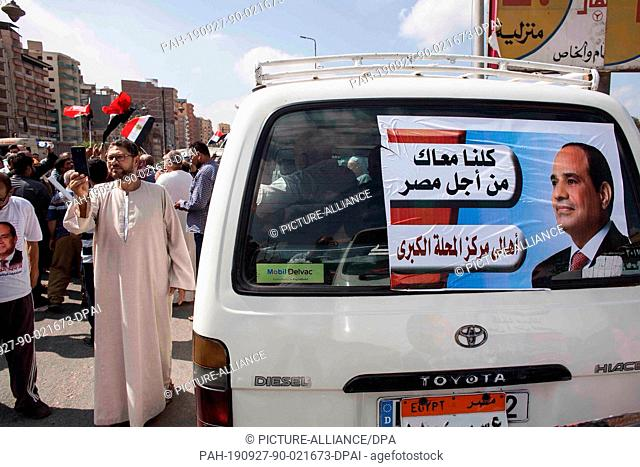 27 September 2019, Egypt, El-Mahalla El-Kubra: A van is seen with a picture of Egyptian President Abdel Fattah el-Sisi as the president's supporters prepare to...