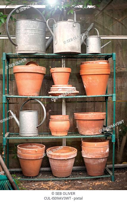 Clay plant pots and watering cans on rack
