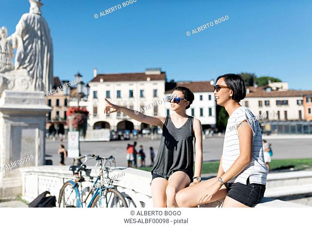 Italy Padua, two young women watching something