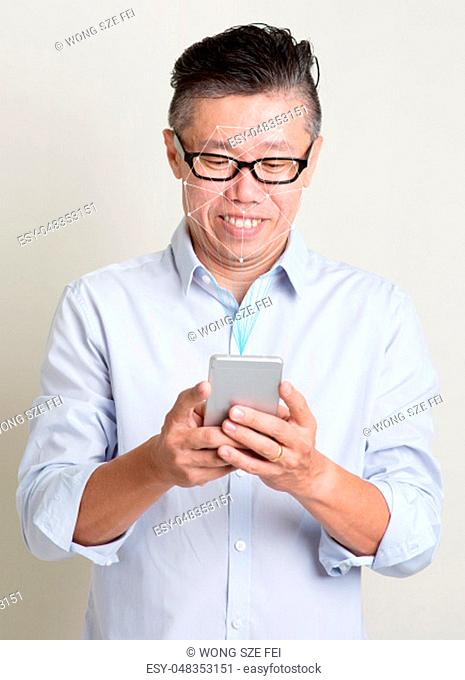 Futuristic and technology. Concept of scanning Asian man face with smartphone for facial recognition