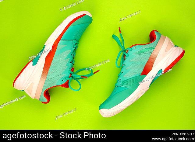 Red, cyan, white pair of new tennis shoes in studio shot over green background. Directly from above