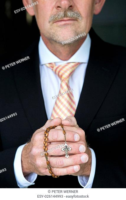 closeup of businessman holding a rosary and praying