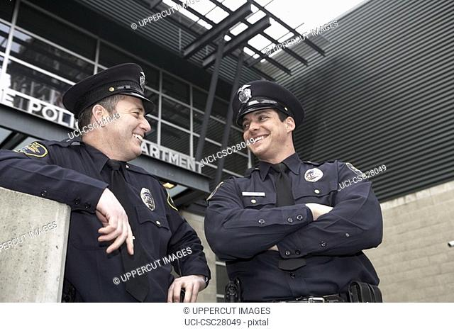 Male police officers talking outside Police Department