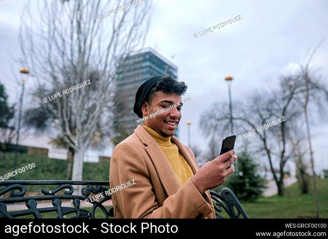 Smiling young man sitting on a bench using cell phone
