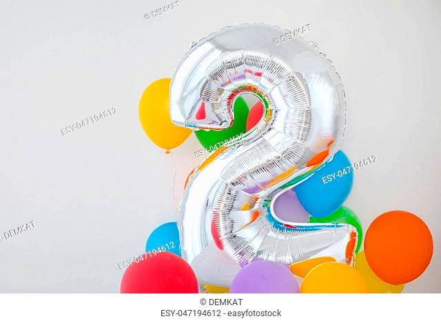 Number 2 two of color balloon on a light background. Birthday balloon for baby with , rainbow color- red, orange, yellow, green, sky blue and fiolet balloons