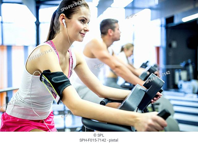 MODEL RELEASED. Young woman listening to music while working out in gym