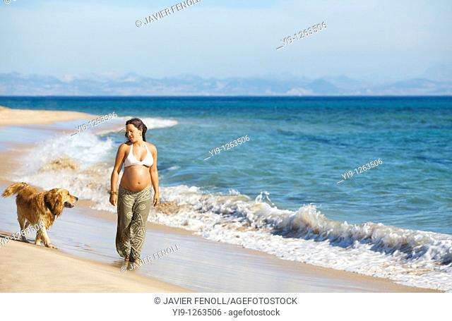 Pregnant woman relaxing on the beach with her dog
