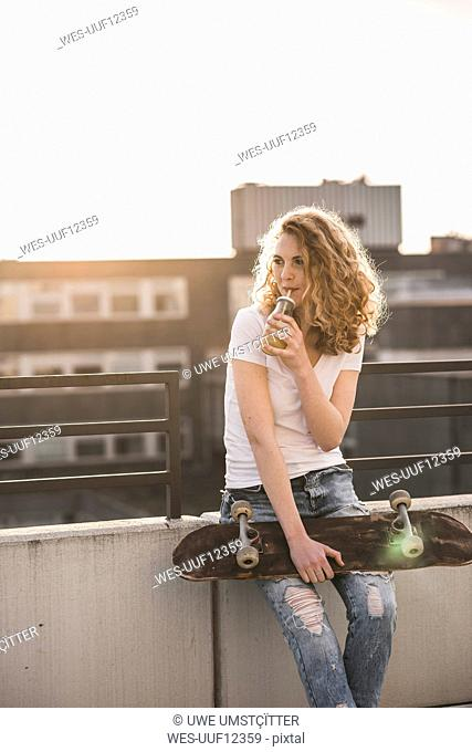 Young woman with skateboard drinking beverage on roof terrace at sunset