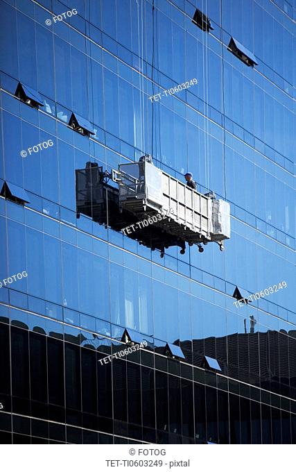 USA, New York, New York City, Manhattan, Window cleaners on scaffolding