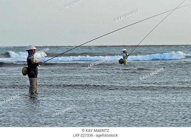Fishermen with fishing rod standing in the water at low tide, Pura Geger, Southern Bali, Indonesia, Asia