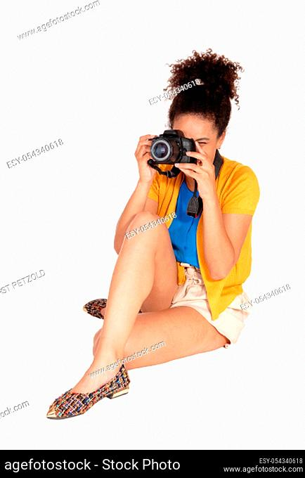 A young multi-racial woman sitting and taking some pictures with her.camera, with her curly black hair, isolated for white background