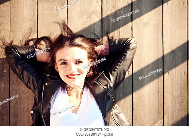 Portrait of young woman lying on wooden decking, hands behind head, smiling, overhead view