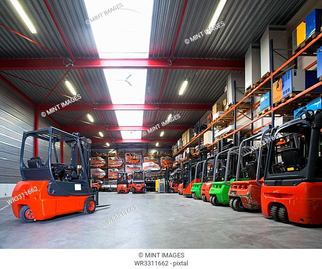 Forklift machinery in a row in warehouse