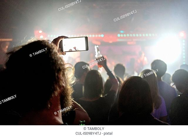 Man taking photograph of concert with smartphone
