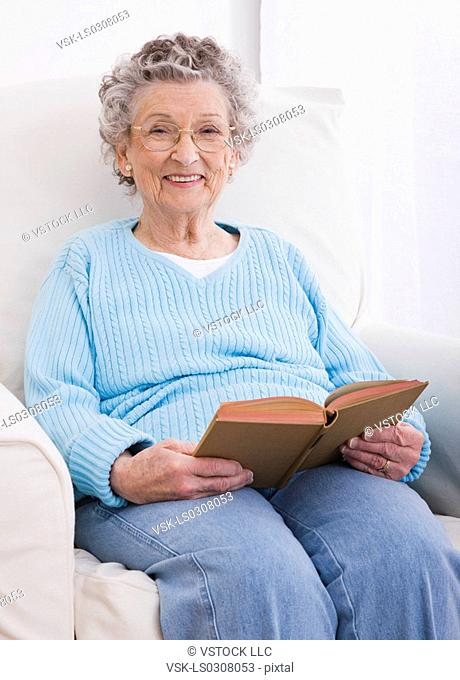 Portrait of senior woman sitting in armchair with book
