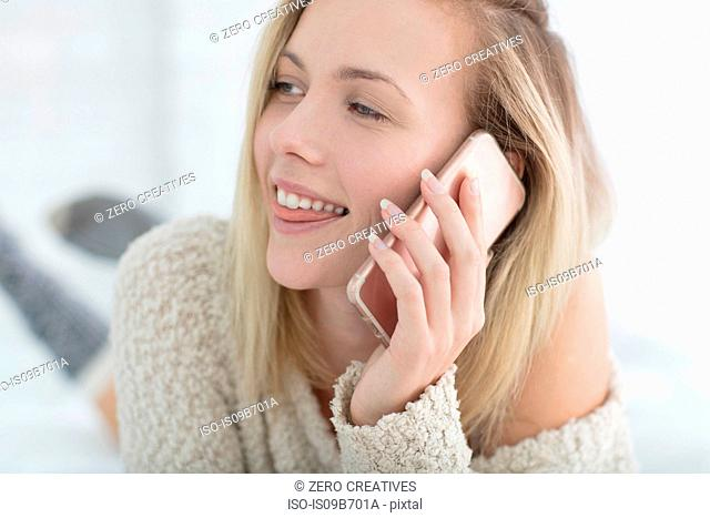 Young woman lying on bed, talking on smartphone